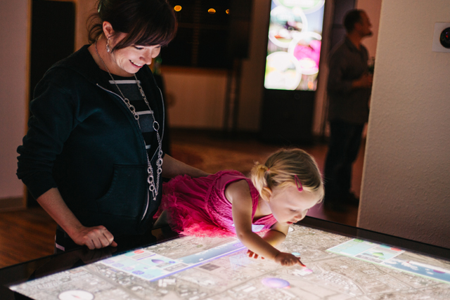 Young girl plays a large-scale touch table based game, piloting hot air balloons to a target.